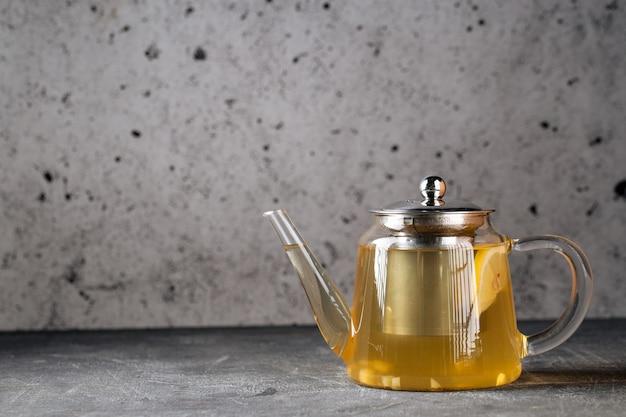ガラスのティーポットにレモンと熱い健康的な緑茶
