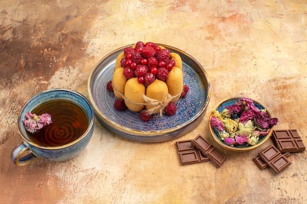 Torta morbida tisana calda con frutta fiori barrette di cioccolato e tovagliolo su tavola di colori misti