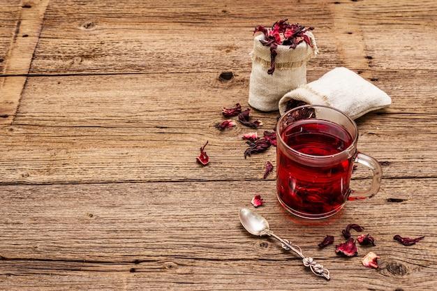 Hot hibiscus tea. dry petals, linen sacks. healthy food and self-care concept.