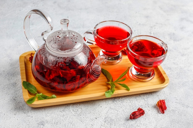 Hot hibiscus tea in a glass mug and glass teapot.