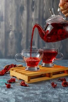 Горячий чай из гибискуса в стеклянной кружке и стеклянном чайнике.