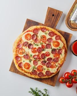サラミ、白いテーブルの上のモッツァレラチーズ、ソーセージとトマトの素朴なディナー、上面図、垂直のホット自家製イタリアンペパロニピザ