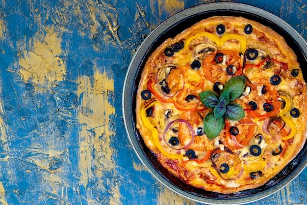 바질, 올리브, 토마토, 햄, 치즈가 들어간 뜨거운 이탈리아 수제 피자. 텍스트를위한 여유 공간