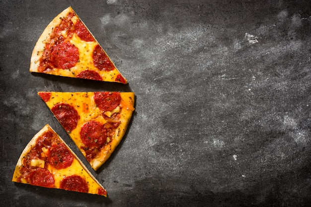 Горячая итальянская пицца пепперони ломтик на черном камне
