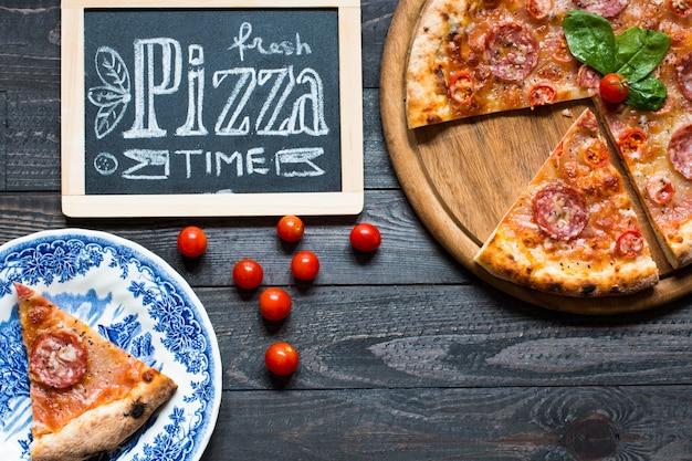 Горячая итальянская пицца на деревенский деревянный столик.