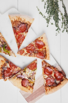 Hot italian pizza with melting tomato, pepperoni and cheese on a white rustic wooden table.
