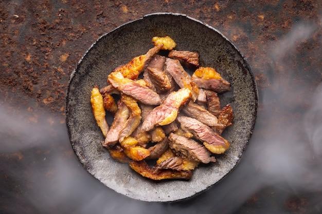 솜케, 위쪽 전망이 있는 녹슨 질감 배경에 있는 와비 사비 스타일 접시에 있는 뜨거운 육즙 얇게 썬 쇠고기 필레 스테이크 고기