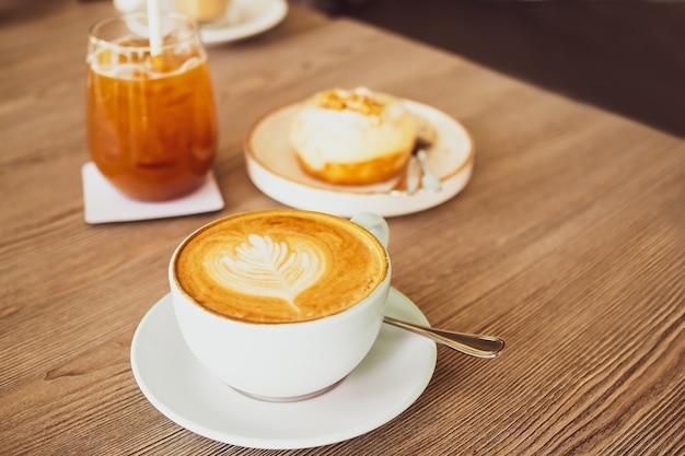 Горячий поздний кофе в белой чашке и ложке на деревянный стол