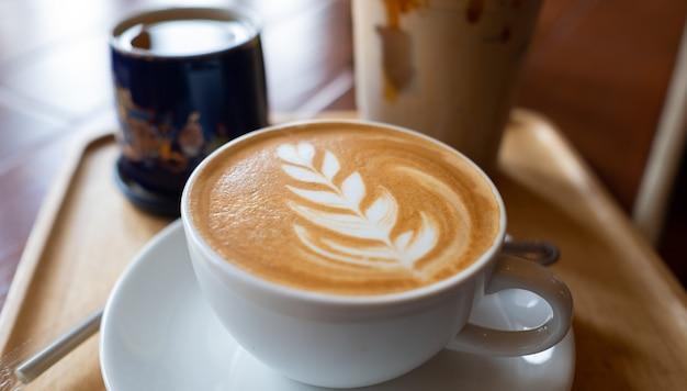 Горячий кофе латте арт на деревянном столе, время отдыха