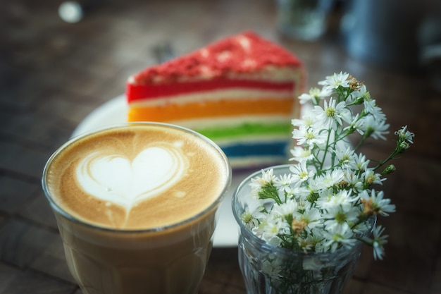 The hot latte art coffee with colorful cake in coffee shop