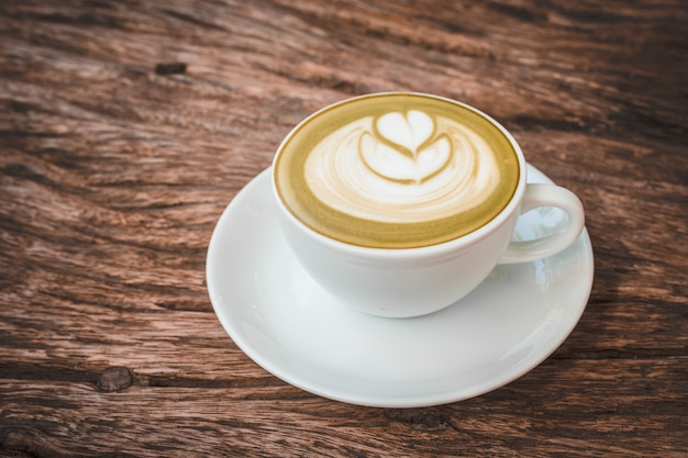 Hot latte art coffee on wooden background