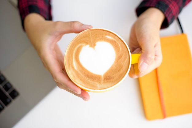 Hot latte art in yellow cup on working desk