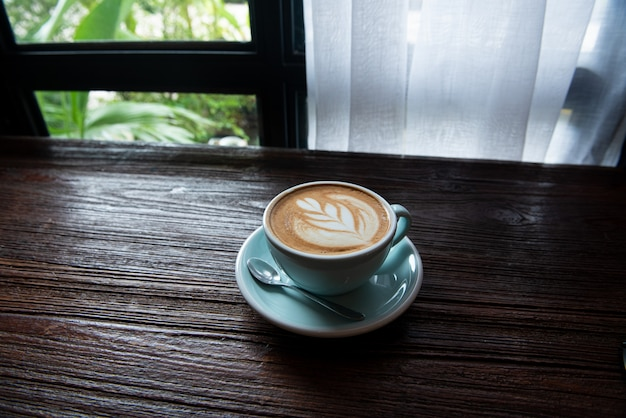 窓際の木製テーブルの上のホットラテコーヒーカップ