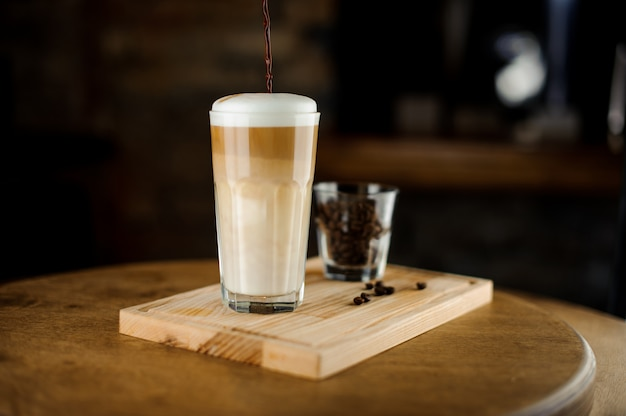 Hot latte coffee in a high glass cup on a wooden board