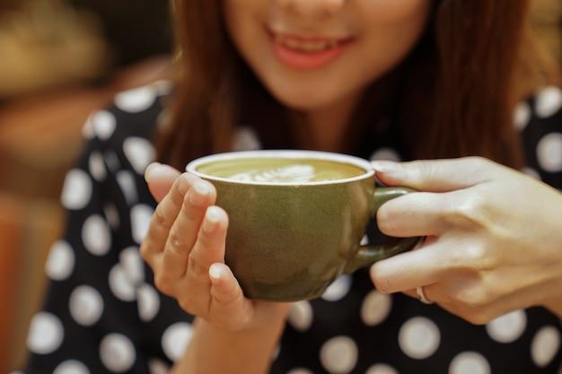 Горячий кофе латте в руке азиатской девушки, сообщение и готово к употреблению.