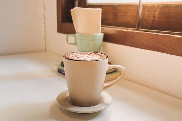 Горячий кофе латте подается в белой кружке на столе утром