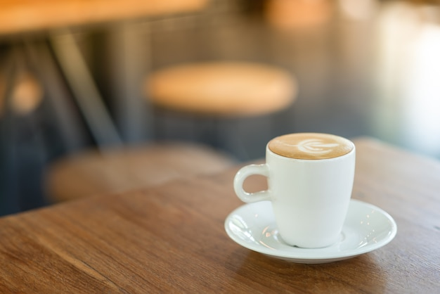 Hot latte is placed on a wooden table in cafe