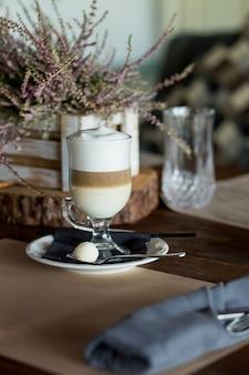쿠키, 지팡이 설탕과 함께 제공되는 어두운 나무 테이블에 맛있는 거품 투명 유리와 뜨거운 라떼 마끼아또 커피. 커피 타임, 맛있는 달콤한 음료. 아침 식사 시간. 레트로 톤 이미지입니다. 낮은 키 어두운 사진입니다.