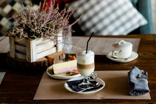 따뜻한 라떼 마끼아또 커피와 맛있는 거품 투명 유리가 있는 어두운 나무 테이블에 과자, 딸기 케이크, 사탕수수 설탕이 제공됩니다. 아침 식사 시간. 레트로 톤 이미지입니다. 낮은 키 어두운 사진입니다.