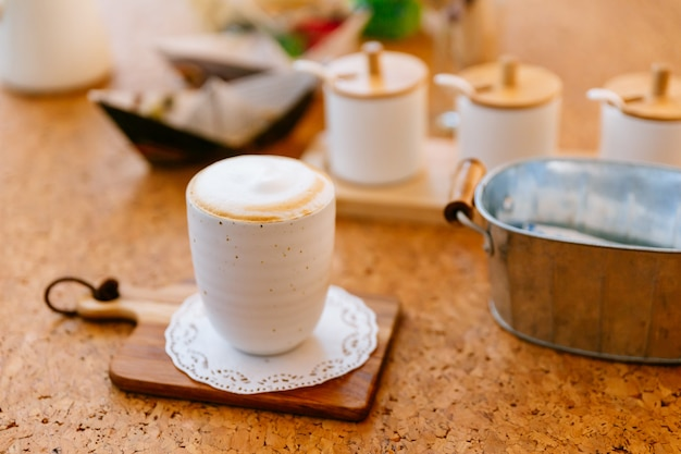 Hot latte served in ceramic cup on wooden plate. smooth white and brown froth.