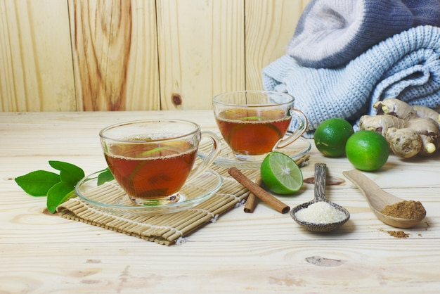 Hot lemon and ginger and cinnamon tea  with craft on wooden table.