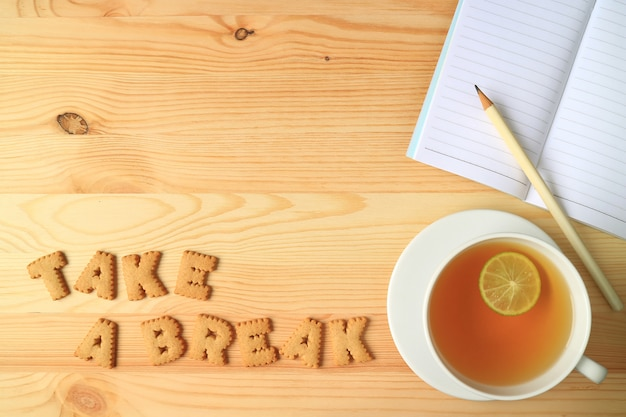 Hot lemon tea, note papers and pencil beside with word take a break