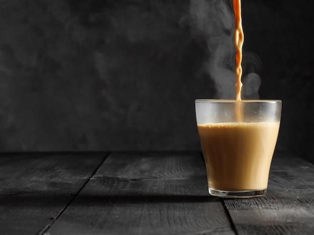 Горячий чай масала наливается в стеклянный бокал. из кружки выходит пар.