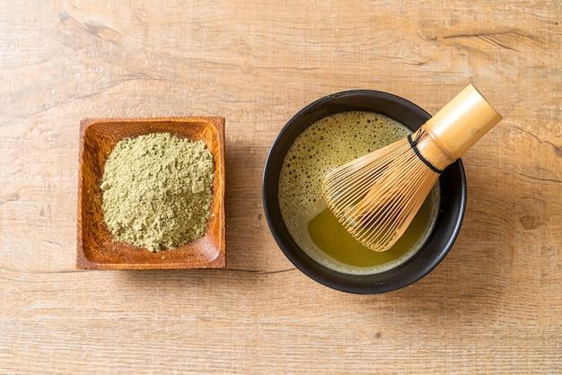緑茶粉と竹泡立て器が入った温かい抹茶緑茶カップ
