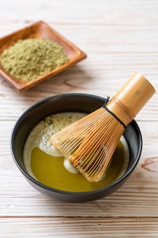 Чашка горячего зеленого чая матча с порошком зеленого чая и венчиком