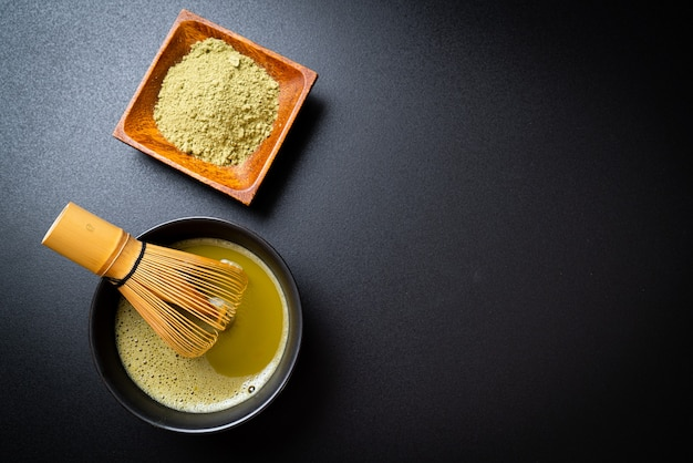 Hot matcha green tea cup with green tea powder and bamboo whisk