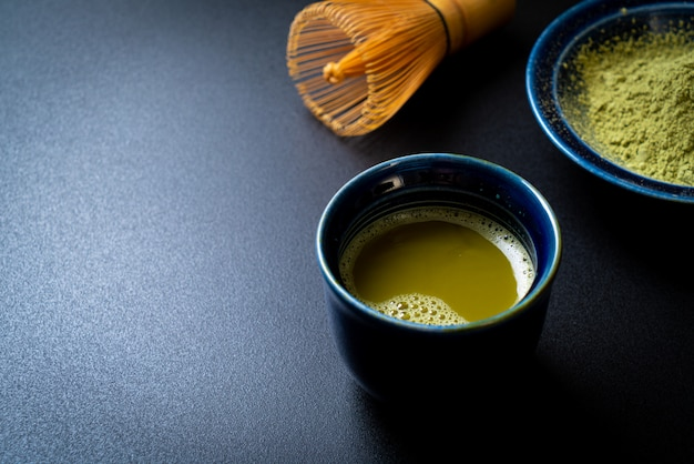 Hot matcha green tea cup with green tea powder and whisk