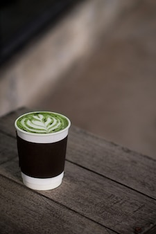 Hot matcha green tea latte take away cup on wood table