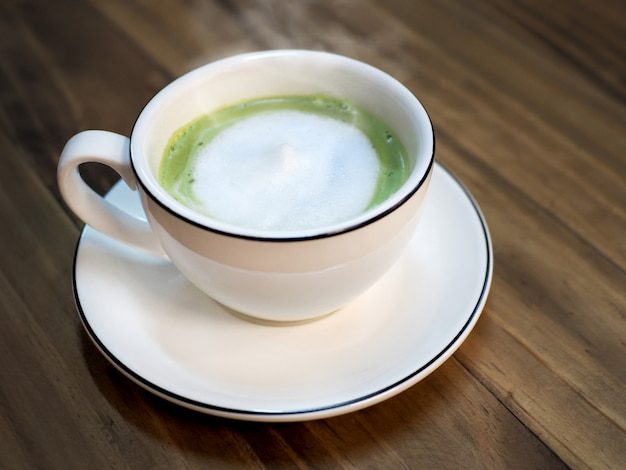 Hot matcha green tea latte with milk foam cup on wood table at cafe - healthy drink.