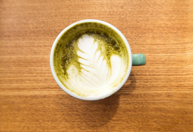 Hot matcha green tea latte on wooden background, top view.