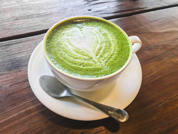 Hot matcha green tea milk latte with creamy milk is heart-shaped pattern