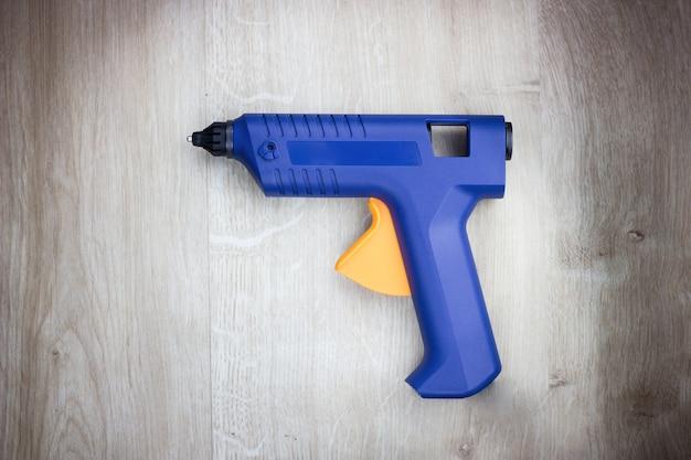 Пистолет-расплав, строительные инструменты. пистолет для плавления силикона, крупный план. изолированные на деревянных фоне.