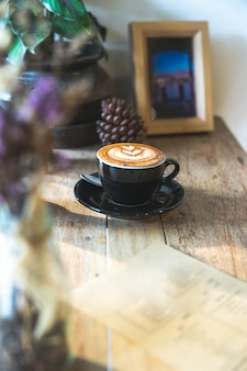 Hot milk cappuccino coffee in black cup on wooden table with copy space