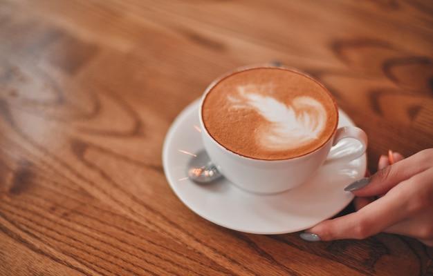나무 테이블에 뜨거운 우유 라떼 아트 커피
