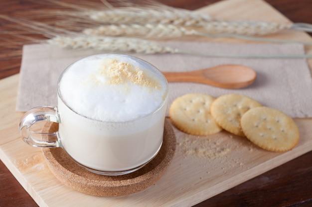 Горячее молоко с печеньем на деревянной тарелке на деревянном столе на завтрак.