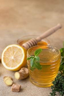 생강 뿌리, 레몬, 꿀, 밝은 콘크리트 배경으로 뜨거운 민트와 백리향 차. 초본 차.