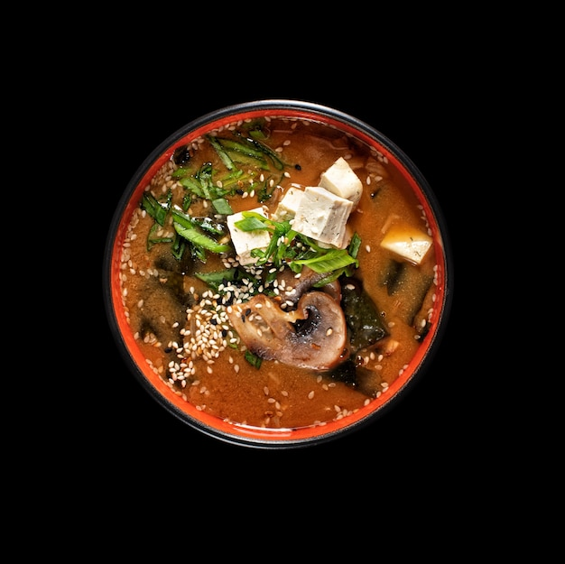 Hot miso soup with seaweed, mushrooms in bowl , top view on a black background for the menu. japanese food.