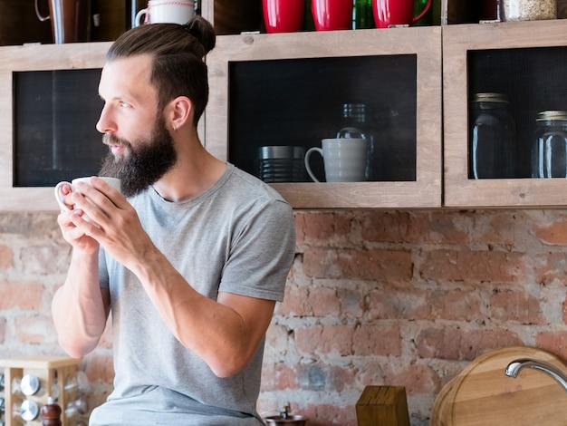 Наслаждение горячим утренним напитком. новый день. восстань и сияй. битник с чашкой, глядя в сторону мышления. созерцание.