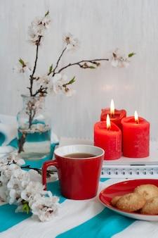 ストライプテーブルクロス、ワックスキャンドル、装飾的なヒトデ、貝殻、ノートの山に自家製クッキーと紅茶の熱いマグカップ