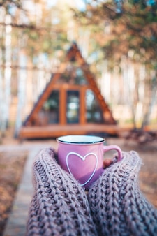 Hot mug of tea warming woman's hands in woollen sweater on background of cozy house at autumn day