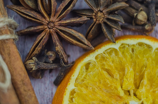 Hot mulled wine drink with lemon, apple, cinnamon, anise and other spices in a glass cup between fir tree branches on wooden cutting board. copy space