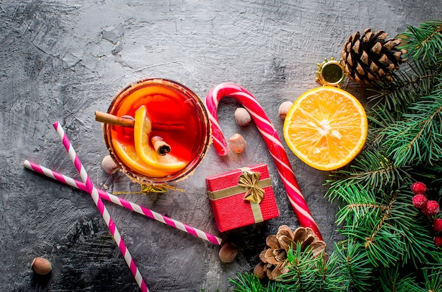 Hot mulled wine drink with orange, and christmas decorations
