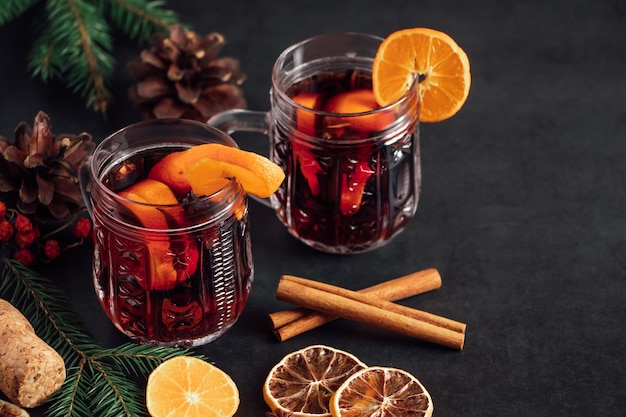 Hot mulled wine in a glass cup. warm winter drink with spices and fruits.