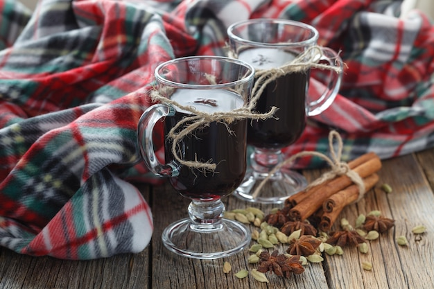 Hot mulled wine in glass on wooden table