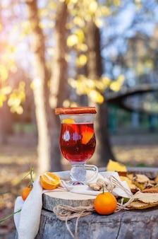 ガラスのホットホットワイン秋の公園でのoutdorsピクニックgluhweinホットワイン垂直写真
