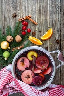 木製のテーブルの上の大きな鍋でホットホットワイン。ワイン、ジュース、スパイス、調味料、フルーツをベースにした香り高い伝統的な冬の飲み物。上面図。